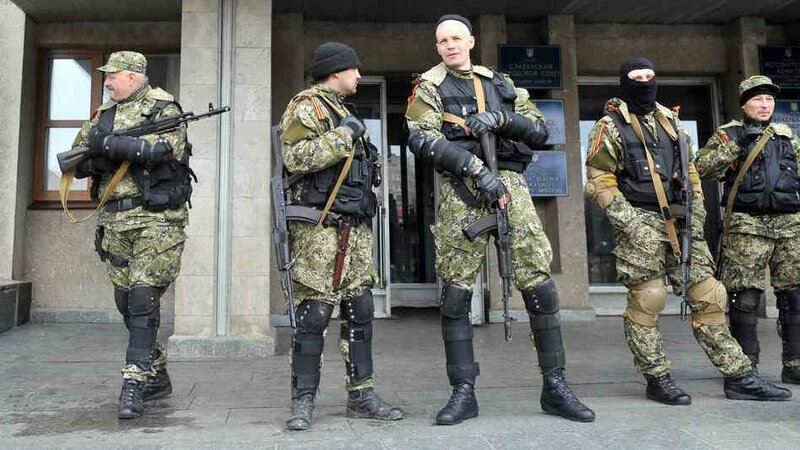 Armed men in military fatigues stood guard Monday outside a regional administration building they seized in the eastern Ukrainian city of Slovyansk.Genya Savilov AFP/Getty ImagesArmed men in military fatigues stood guard Monday outside a regional ad