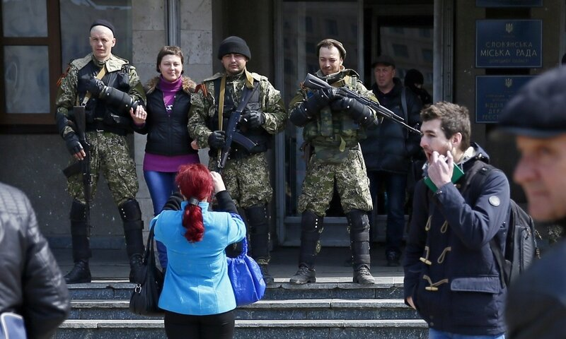 A local resident poses for a picture with pro-Russian armed men standing guard outside the mayor's office in Slaviansk