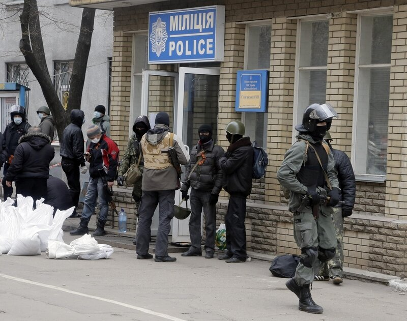 Armed pro-Russian activists occupying the police station in the eastern Ukraine town of Slovyansk carry riot shields on in Slovyansk, Saturday, April 12, 2014. Pro-Moscow protesters have seized a number of government buildings in the east over the past we