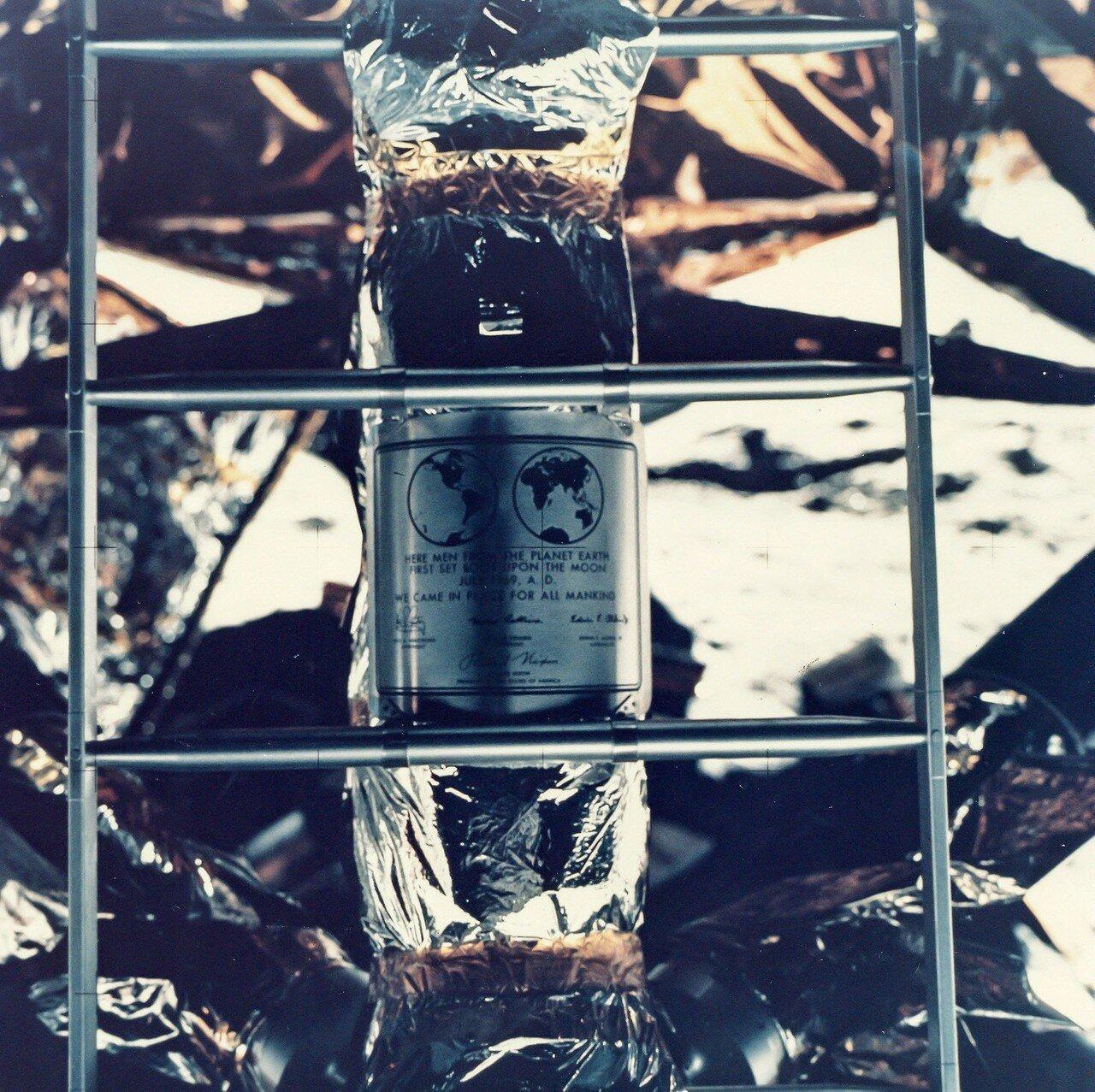 Затем они вдвоём открыли мемориальную табличку на опоре лунного модуля, сняв с неё металлическую крышку. Армстронг подробно описал, что на ней изображено, и прочитал вслух надпись, после чего отнёс телекамеру примерно на 20 м от «Орла» к