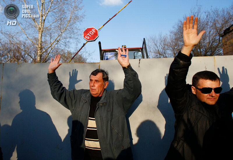 Pro-Russia protesters hold their hands up in the air in front of an Ukrainian airbase in Kramatorsk