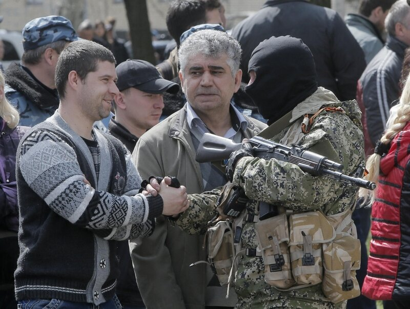 A masked pro-Russian gunman speaks with local residence in downtown Slovyansk on Wednesday, April 16, 2014. The troops on those vehicles wore green camouflage uniforms, had automatic weapons and grenade launchers and at least one had the St. George ribbon