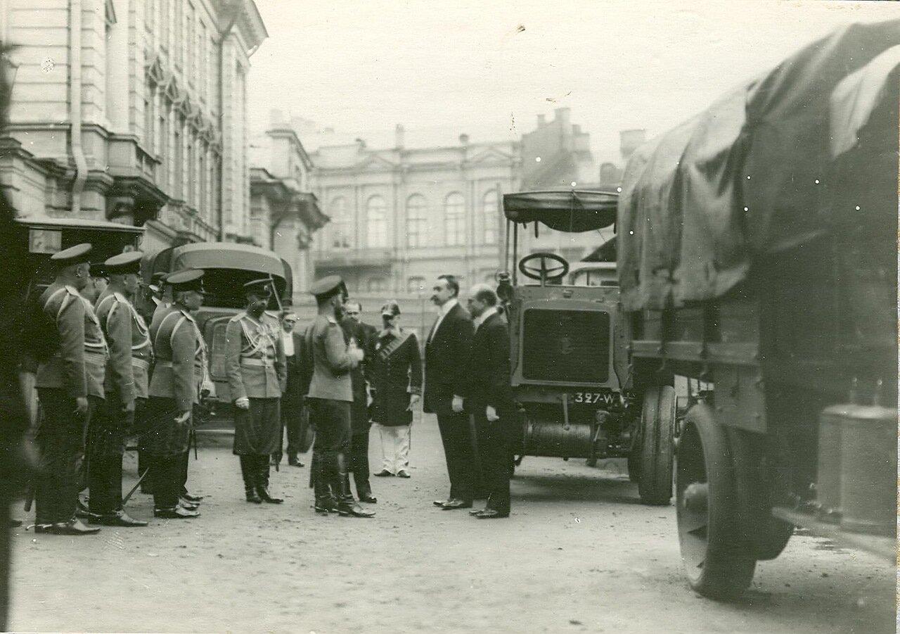 22. Император Николай II и сопровождающие его лица осматривают  новую модель автомобиля у входа в выставочный зал