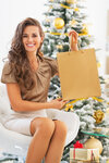Smiling young woman showing shopping bag near christmas tree