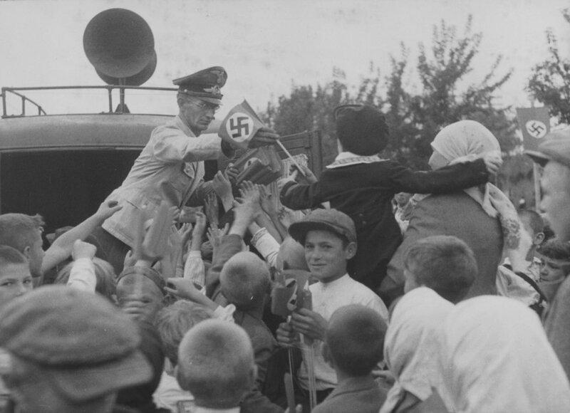 Сотрудник рейхсминистерства оккупированных восточных территорий (Reichsministerium für die besetzten Ostgebiete — RMfdbO) раздает флажки со свастикой жителям Киева во время празднования второй годовщины захвата города немецкими войсками.