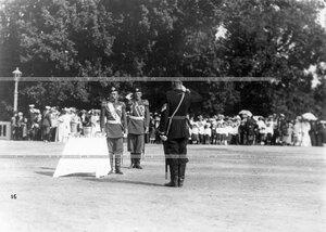 Император Николай II с группой офицеров на площади у столиков с чарками вина во время полкового парада.