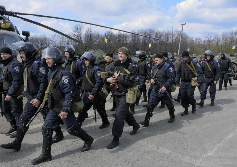 Members of the Ukrainian Interior Ministry walk past a helicopter and armored personnel carriers at a checkpoint in Izium