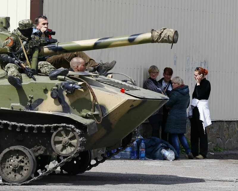 People stand near armed men on an armoured personnel carrier in Slaviansk