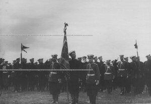 Офицеры и строй солдат с полковым знаменем на параде.