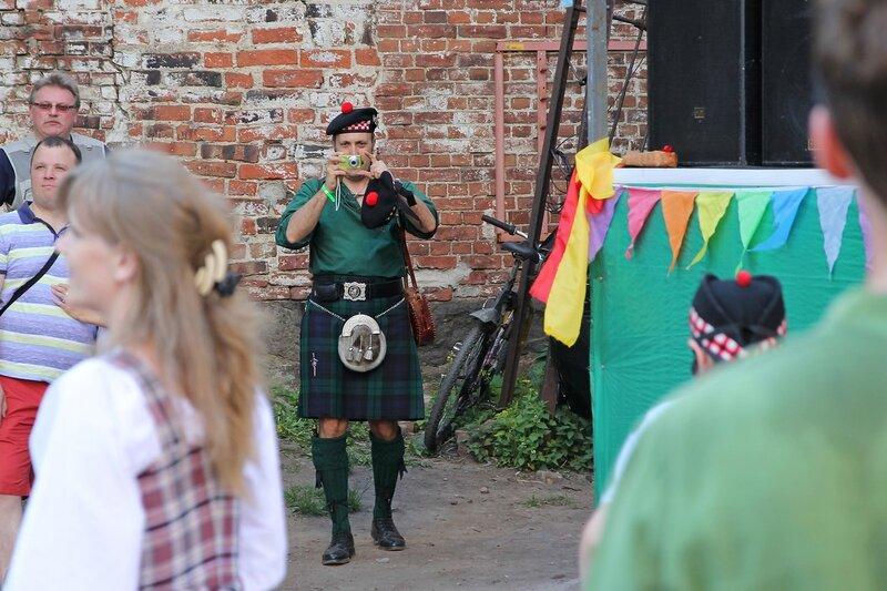 участник фестиваля «Майское дерево 2014» - шотландец в берете с помпоном и килте, держащий фотоаппарат