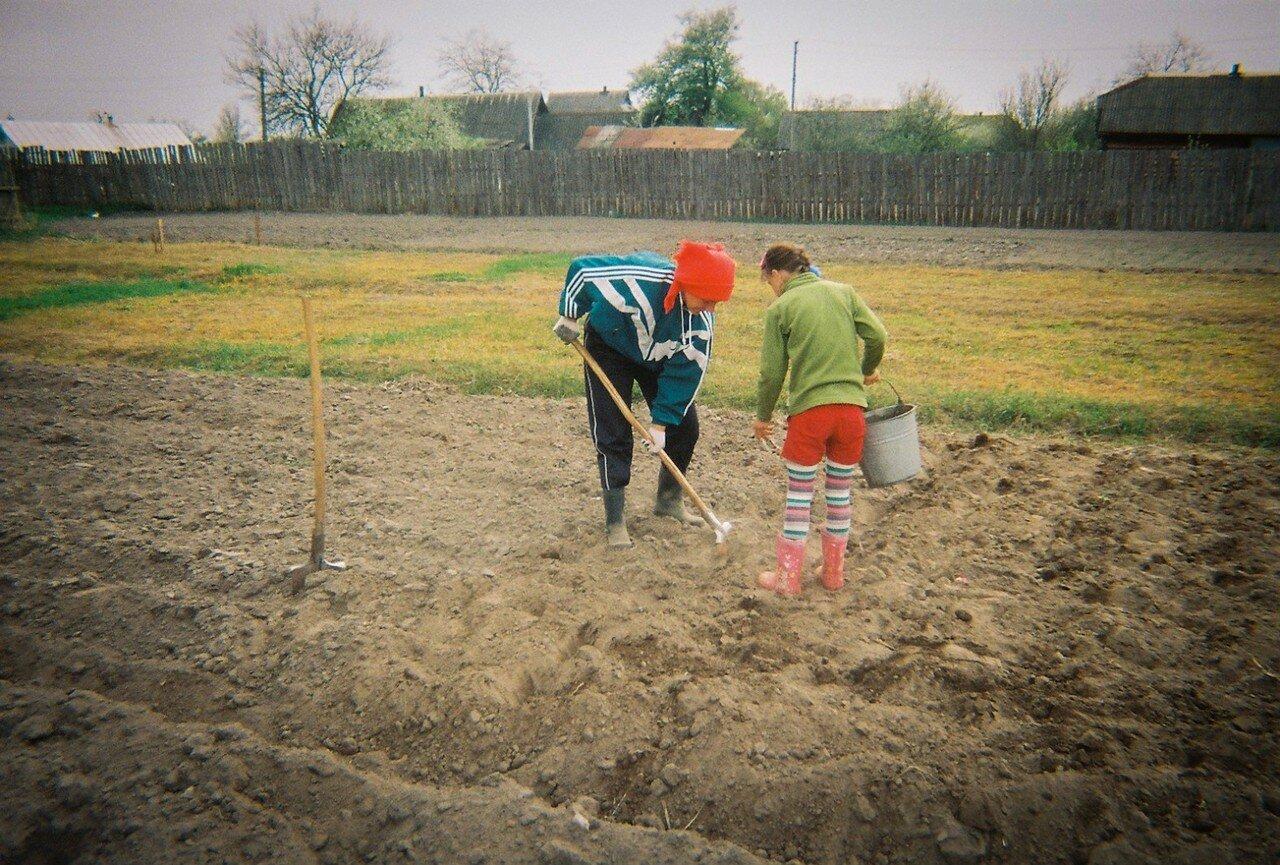 Мать с дочерью сажают в апреле картофель