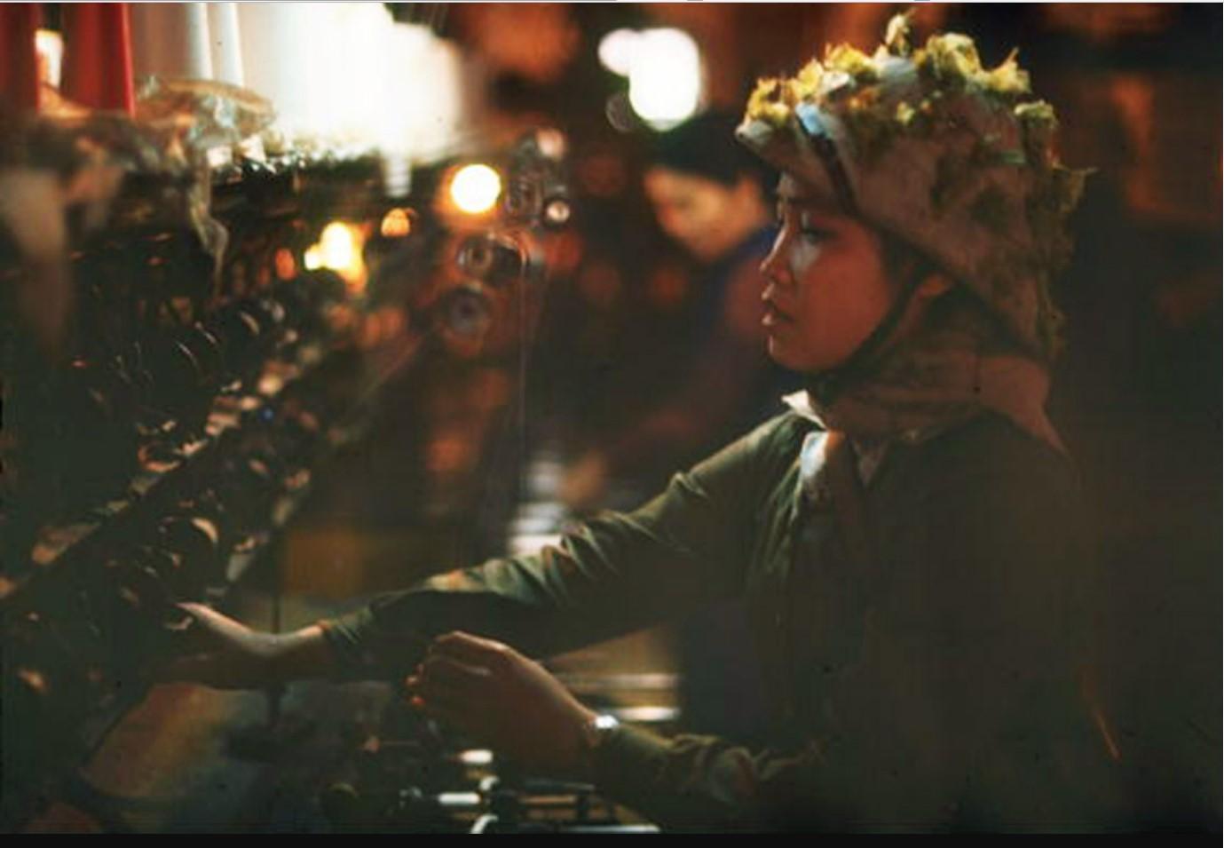 Женщина за ткацким станком в камуфляжном шлеме и винтовке