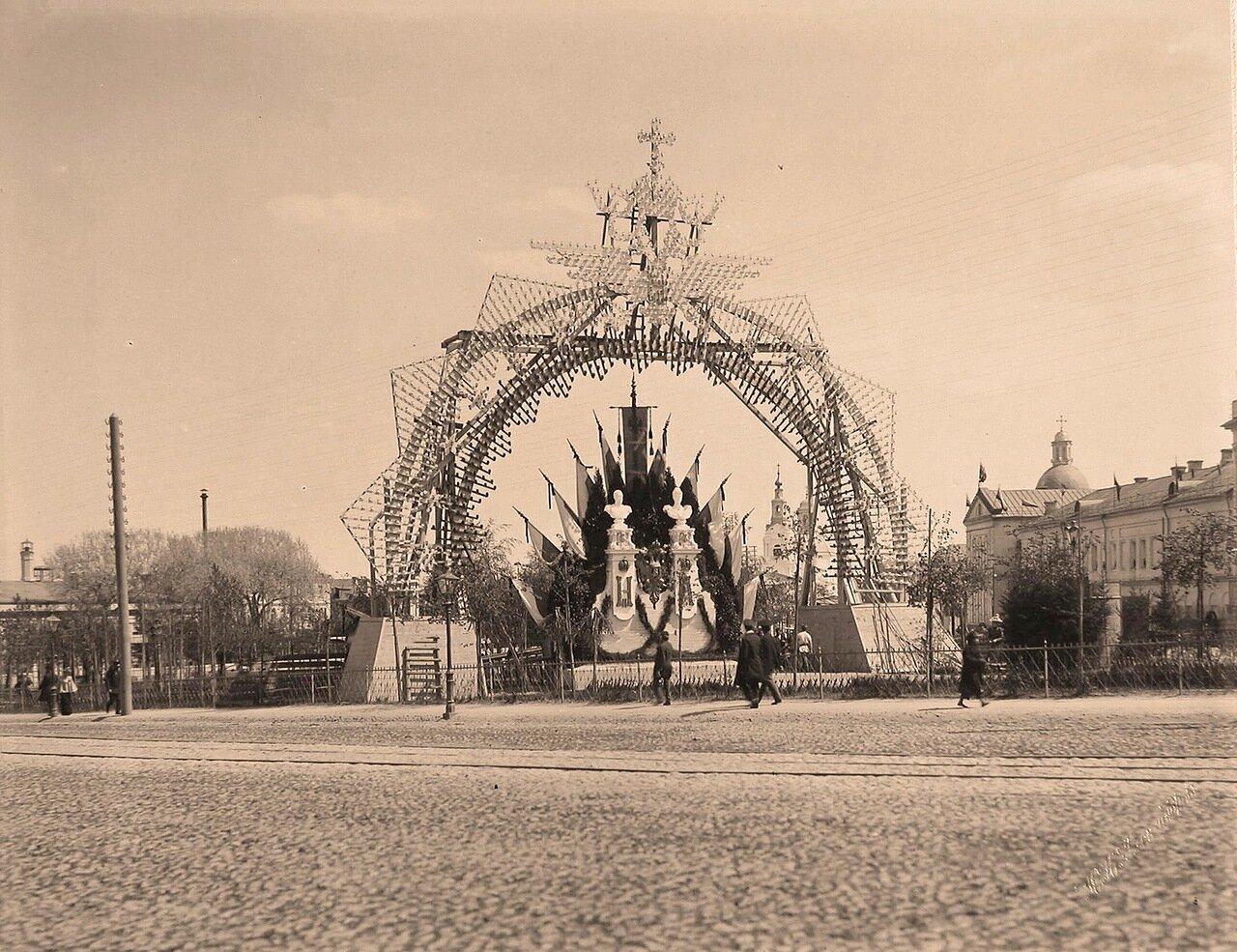 Вид одной из арок, украшенной флагами, бюстами императора и императрицы, иллюминацией, установленной на одной из площадей города