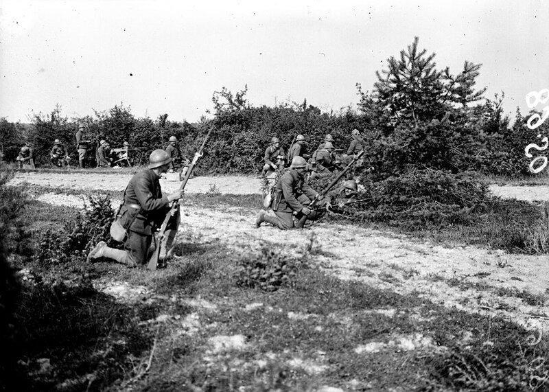 Des grenadiers-voltigeurs du Régiment de Marche de la Légion Etrangère (RMLE) à l'entraînement au camp de Dampierre. L'un d'eux s'apprête à tirer une grenade V.B (Vivien-Bessière) à l'aide du tromblon lance-grenades monté sur son fusil Lebel modèle 1886/9
