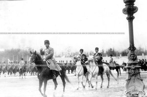 Император Николай II в сопровождении казаков объезжает полк, выстроившийся для парада.