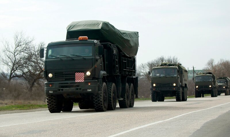 Military vehicles, believed to be Russian, drive on the road near Bakhchisaray