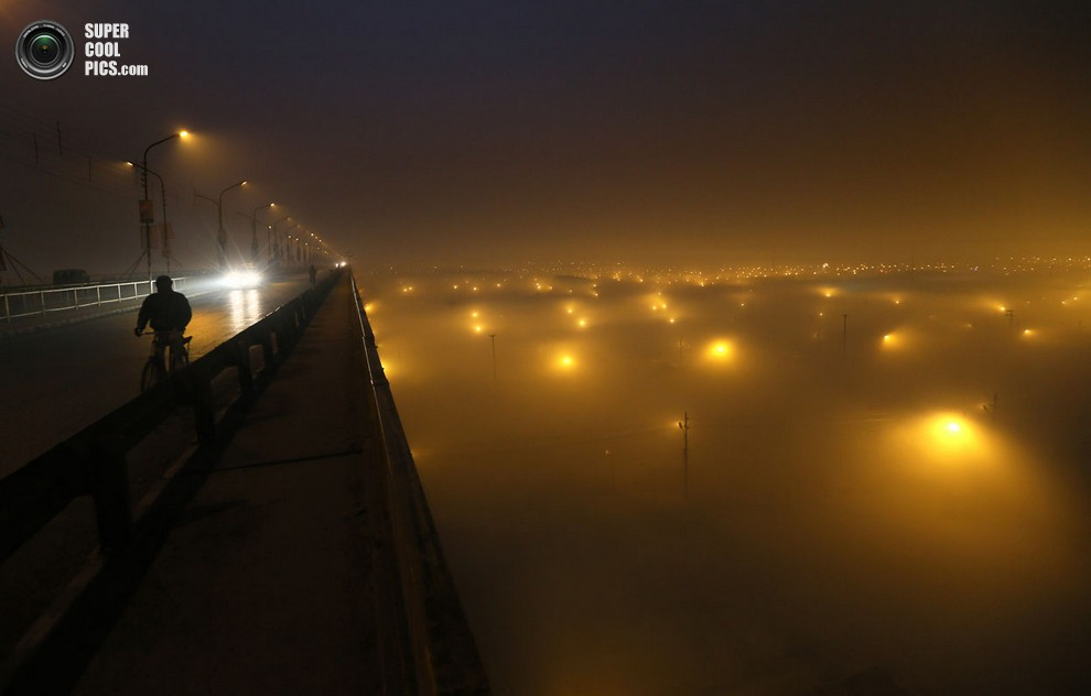 Велосипедист едет по мосту, под которым разбит многомиллионный лагерьучастников Пурна-кумбха-ме