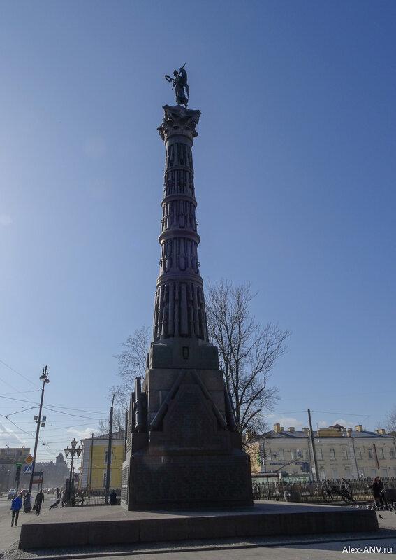 На верху колонны расположен гений с лавровым венком в протянутой руке, увенчивающий победителей.
