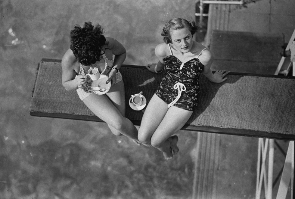 12th May 1938:  Two women having tea on the diving board at Finchley swimming pool, London.  (Photo by J. A. Hampton/Topical Press Agency/Getty Images)
