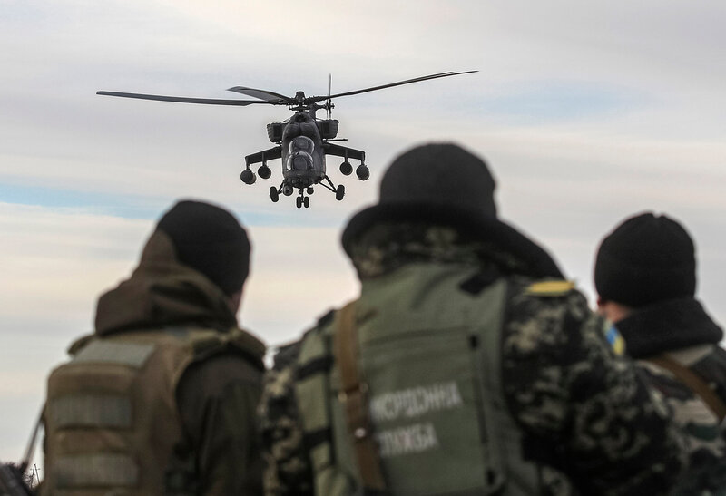 Russian army MI-35 military helicopter patrols the area as Ukrainian servicemen guard a checkpoint near the village of Strelkovo in Kherson