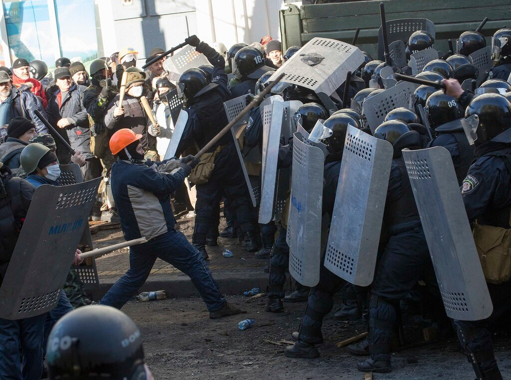 Interior Ministry members clash with anti-government protesters during a rally in Kiev
