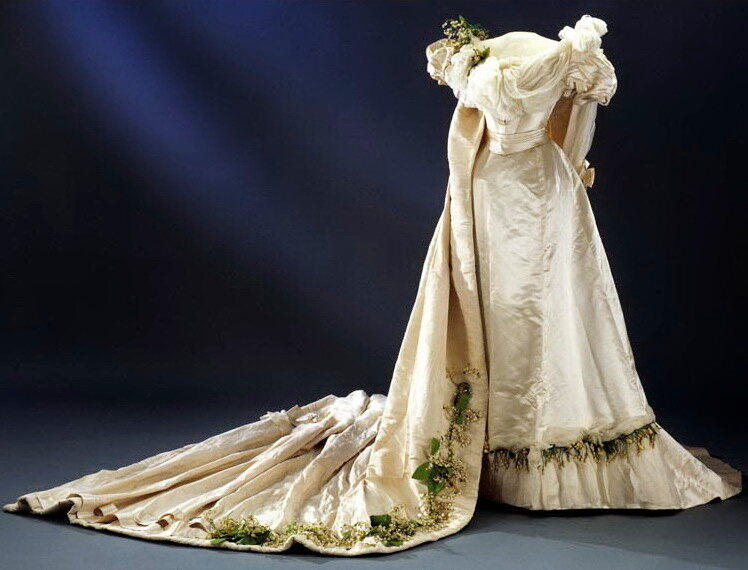 Wedding dress, 1897. Ivory atlas with white silk taffeta over bust and satin ribbon at waist. Yellow & white orange blossom and lily of the valley in wax & fabric attached to shoulder, hem, & train. Train of ivory silk rep (possibly moire) lin