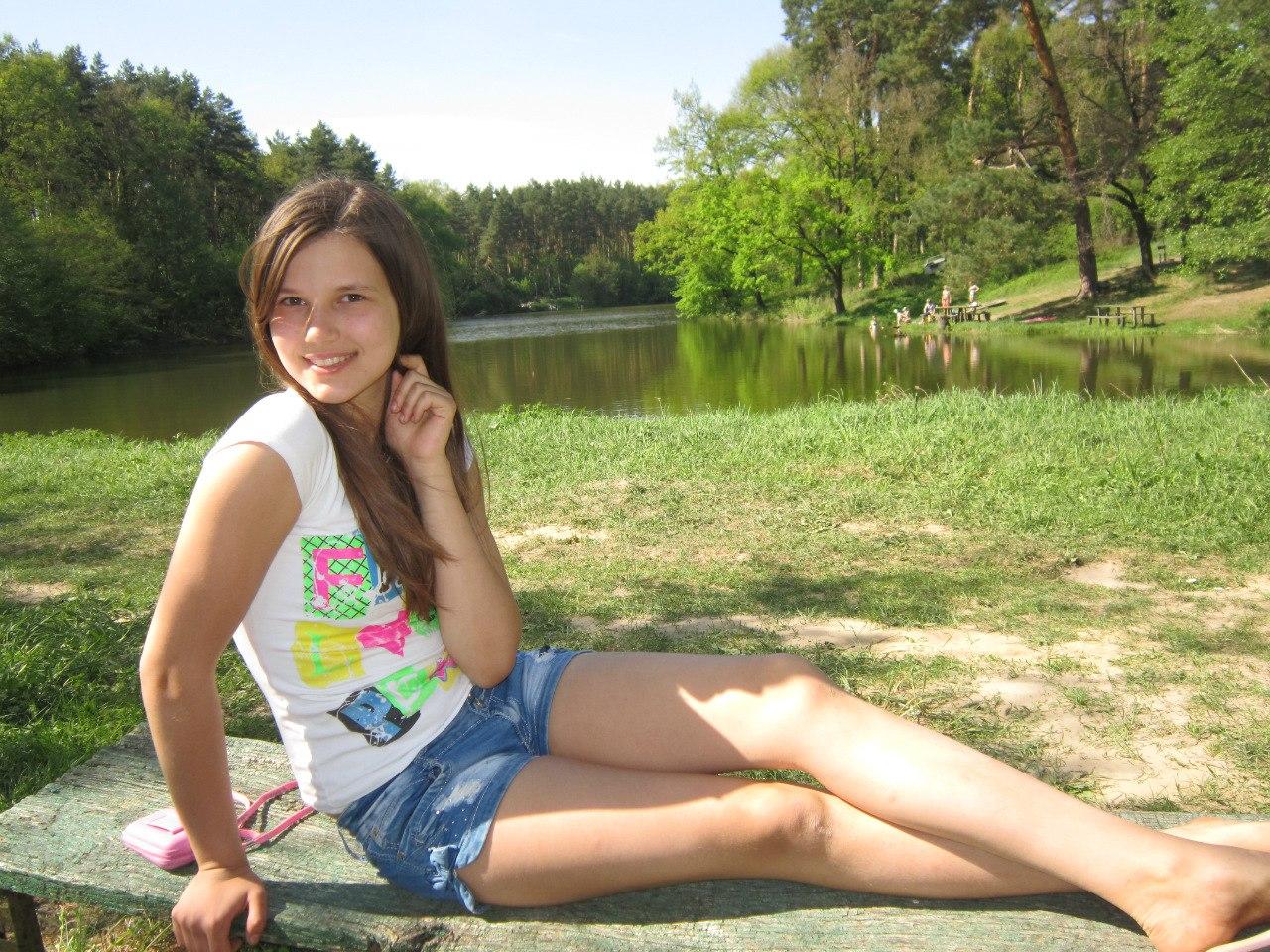 Девушка с красивой улыбкой  на деревянной скамейке