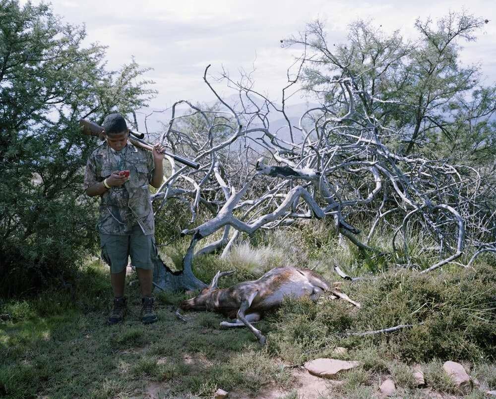 Юный охотник с сотовым телефоном и застреленной антилопой, Восточный Кейп, Южная Африка