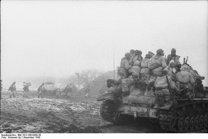 Russland-Süd (Ukraine).- Panzer IV mit aufgesessenen Soldaten (Gebirgsjäger?) auf einem Feld, im Hintergrund Infanterie in Linie marschierend; PK KBZ HGR SüdukraineDepicted place Russland-SüdDate December 1943Photographer Scheerer (e)Russia-Sout