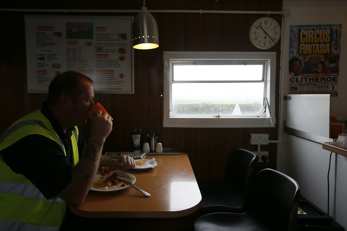 A worker drinks a cup of tea in a roadside cafe along the A59 near Sawley