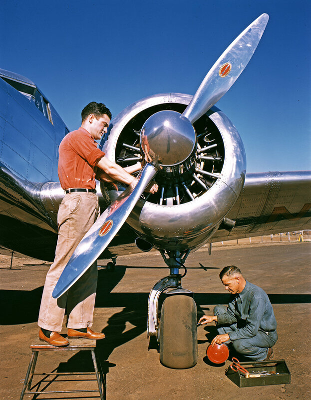 An aviation mechanics making adjustments to the propeller and wheel of a Lockheed Model 12A Electra Junior, belonging to Byrd-Frost, Incorporated, at Dallas Love Field Airport. March 1940