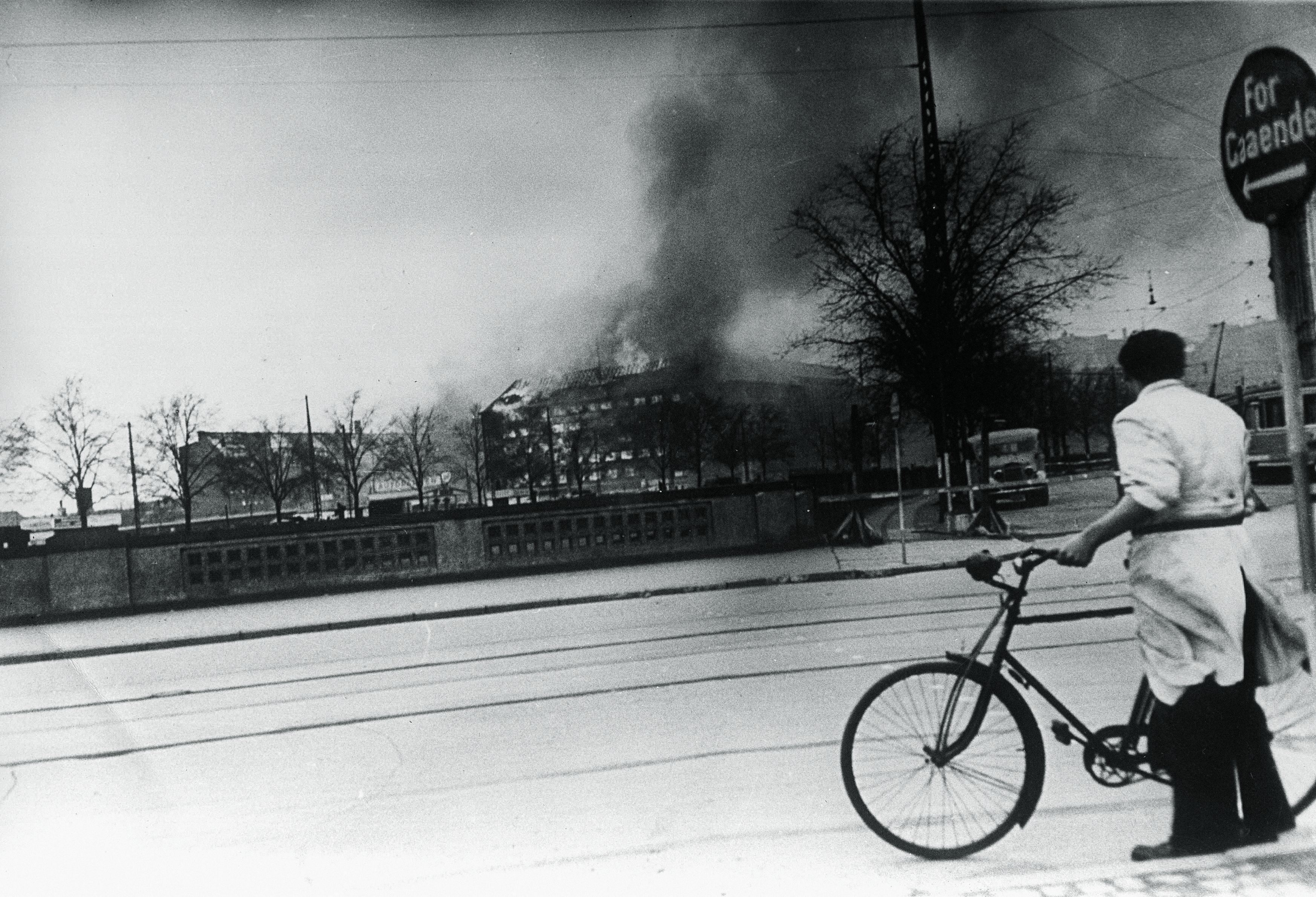 1944. Велосипедист смотрит на горящий «Шеллхаус» (здание Гетапо) после атаки RAF. 18 апреля