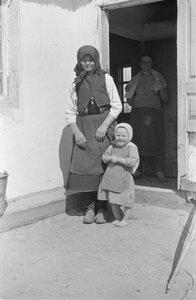 Маленькая девочка с бабушкой перед входом в дом