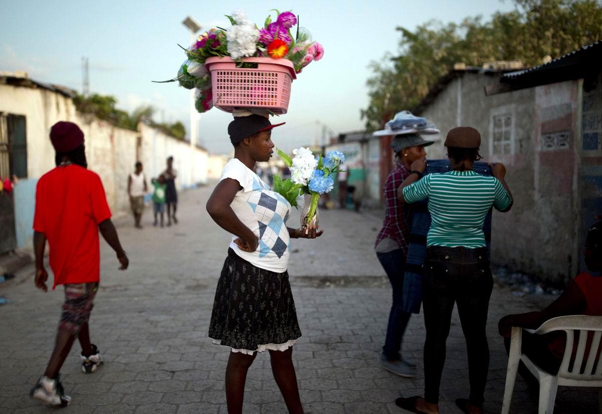 С цветочной клумбой на своей голове: Гаитянская уличная торговка цветами