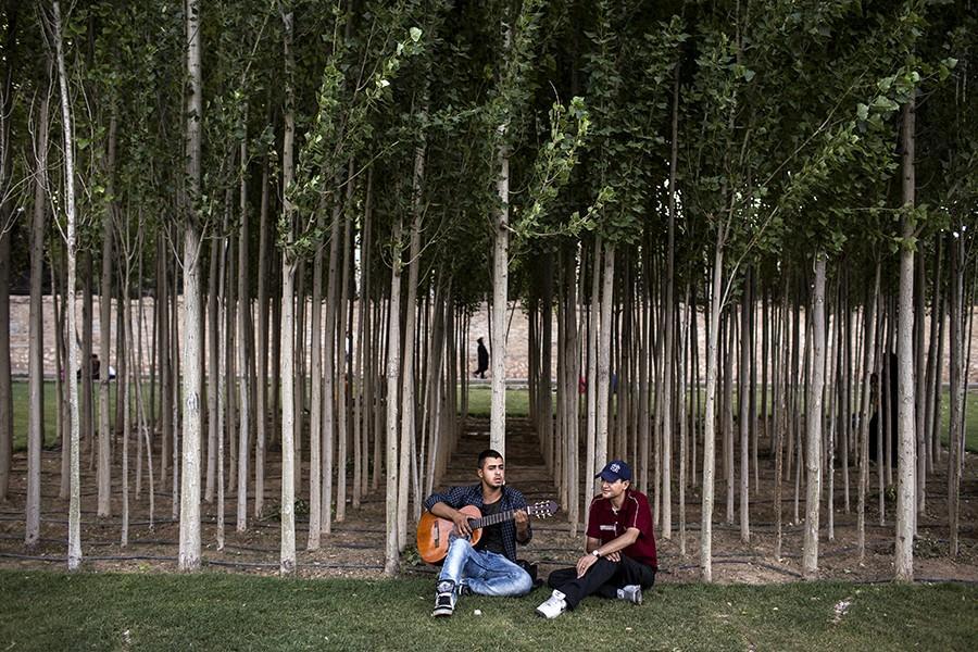 11. Парень играет на гитаре в парке города Шираз.