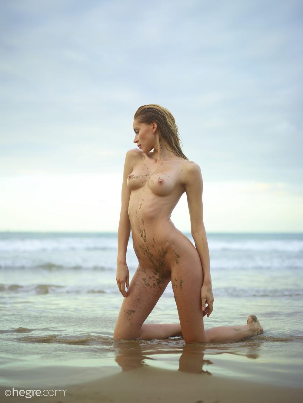 Голая Соня копается в песочке на пляже