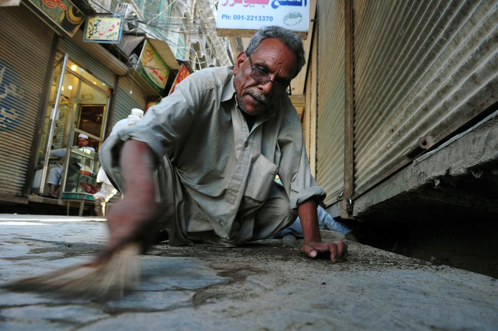 25. Джевед Масих сметает песок с тротуара в поисках золота на рынке золота в Пешаваре, 3 июля 2011.