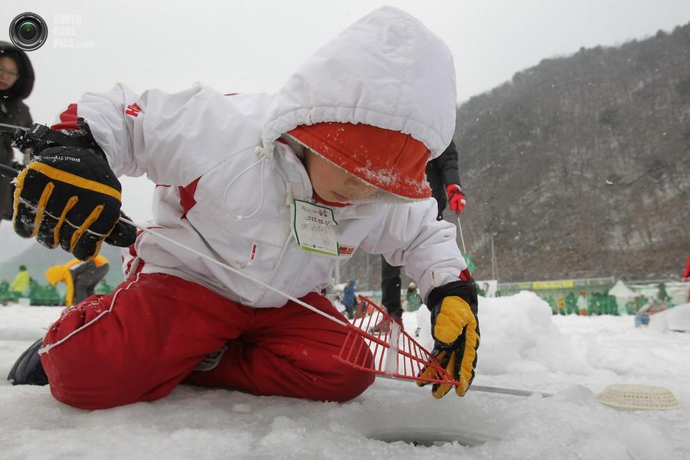 Ребёнок смотрит в лунку, выжидая форель. (Chung Sung-Jun/Getty Images)