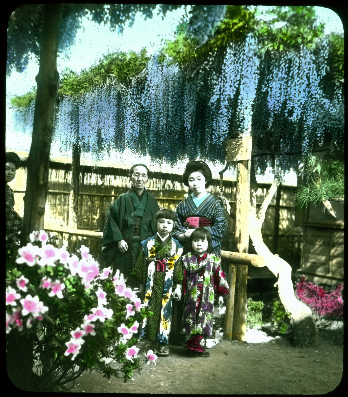 Семья в традиционных одеждах в саду против забора