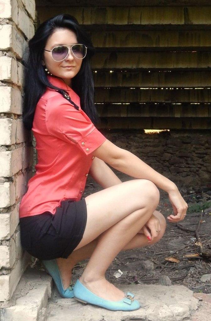 Темноволосая красотка в красной рубашке  на ступеньках