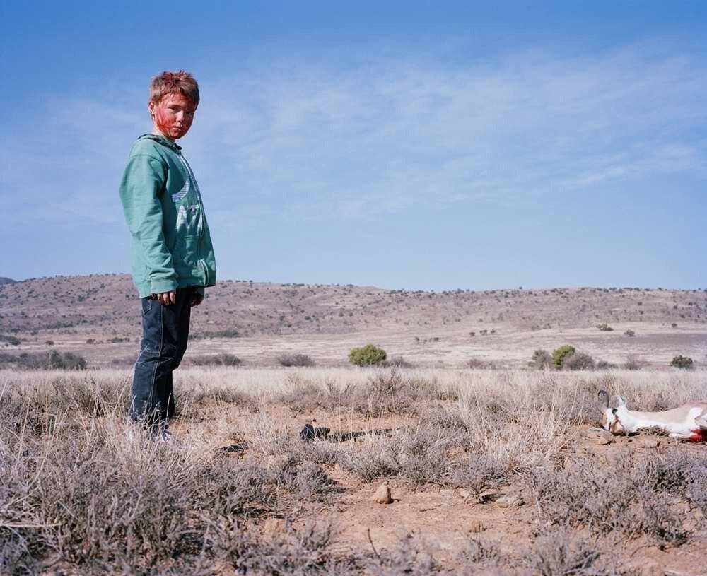Юный охотник с лицом, испачканным кровью, с убитой антилопой, Южная Африка