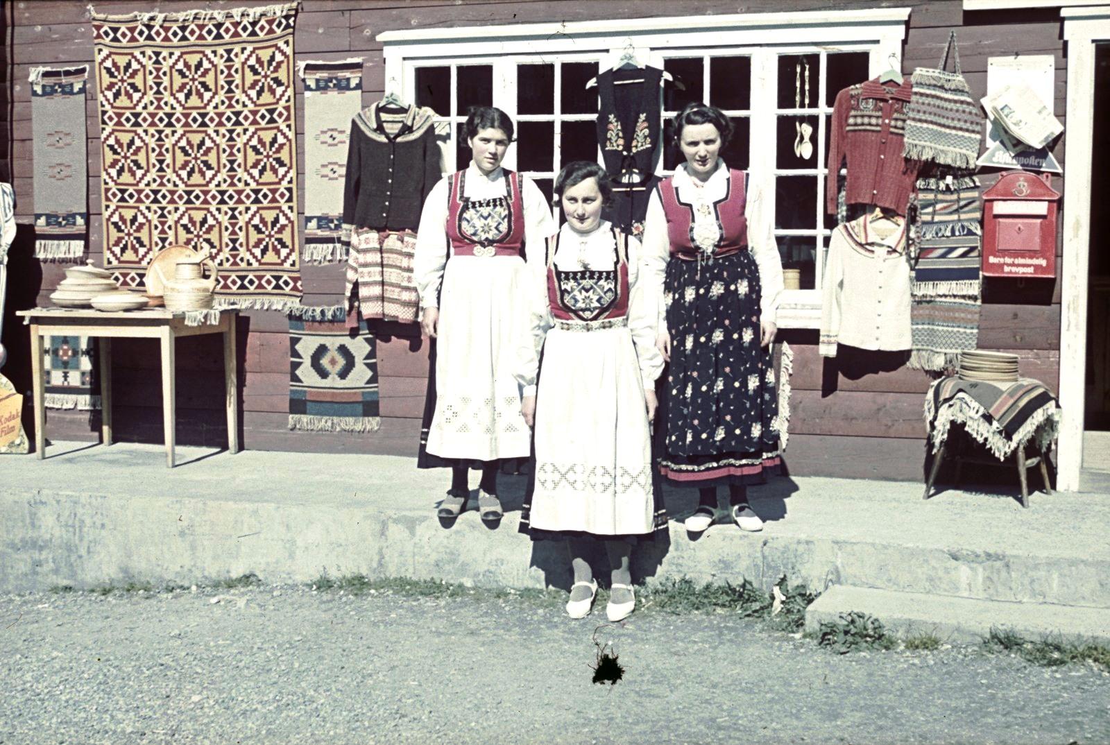 Три молодые женщины в национальных костюмах возле сувенирного магазин