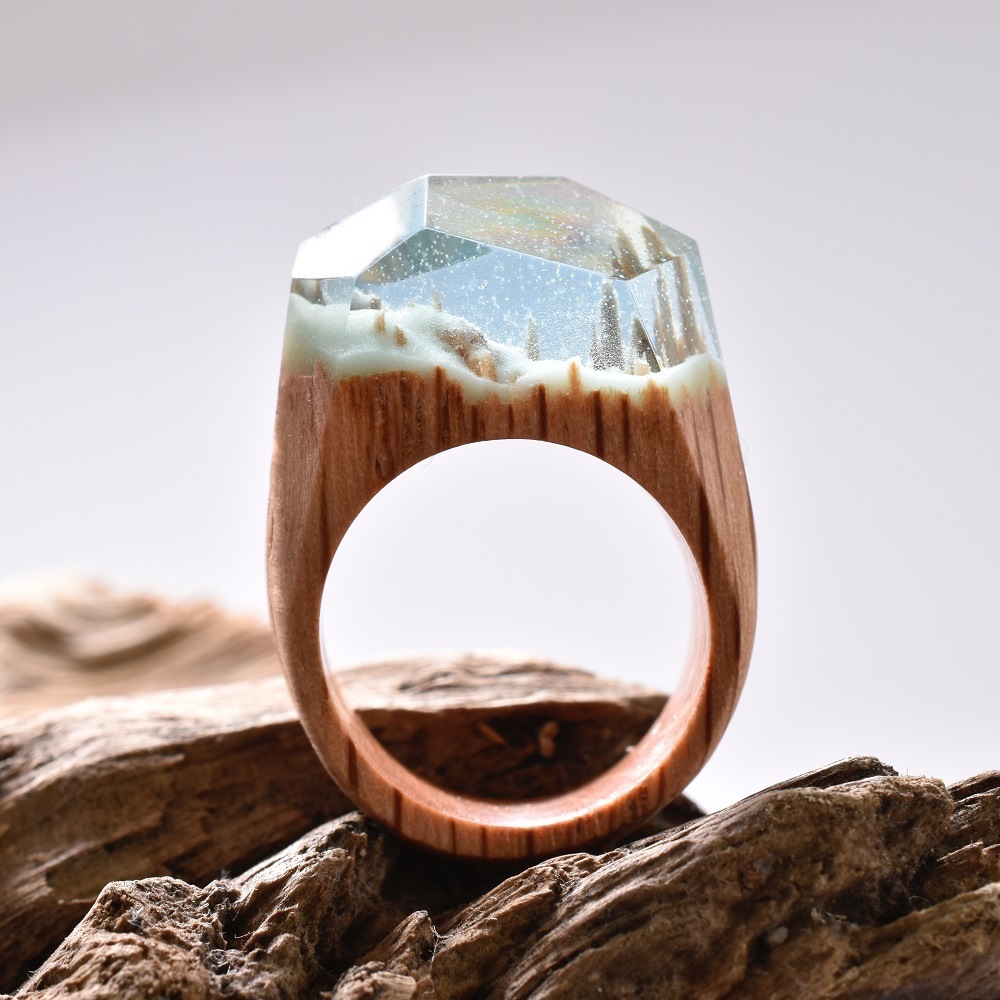 Formed from wood, resin, and beeswax, Canadian jeweler Secret Wood forms tiny worlds within the spac
