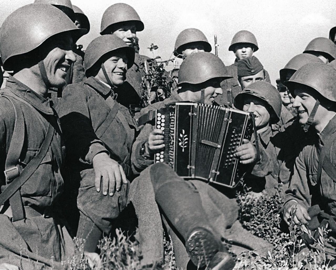 Действующая армия. В минуты отдыха бойцы слушают гармониста Пантахова