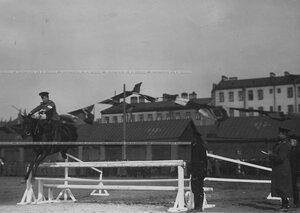 Офицер на лошади в прыжке через препятствия во время конных состязаний.