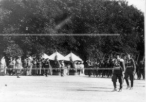 Полки проходят маршем мимо императора Николая II, цесаревича Алексея и членов императорской фамилии.