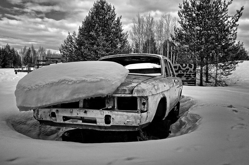 Корпус автомобиля Волга под слоем снега на тренировочном полигоне черно-белый