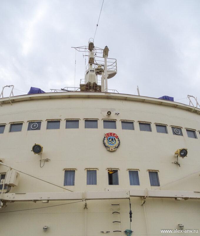 В завершение экскурсии мы отправились на нос корабля. На рубке красуется герб СССР. Ряд окон под ним - это каюта капитана. а выше - окна рулевой рубки.