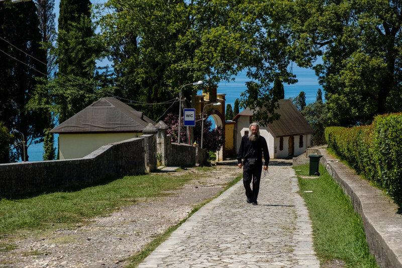 служитель храма поднимается по дороге к храму, Новый Афон 2017