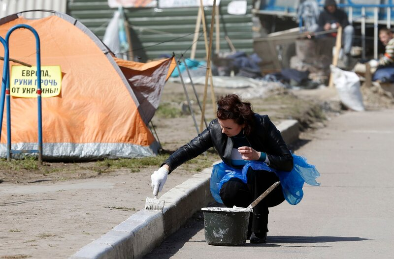 A pro-Russian supporter paints a border in her camp at the seized office of the SBU state security service in Luhansk
